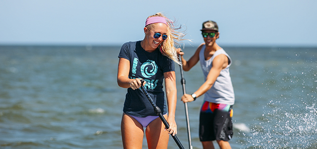 Splash! Ellisa from Koru Village leads the group Stand Up Paddleboarding.