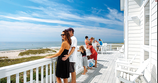 A family enjoys a beautiful sunny day watching dolphins from the deck of their Hatteras Island vacation home, Summer Solstice an oceanfront rental home in Hatteras Village on the Outer Banks of North Carolina